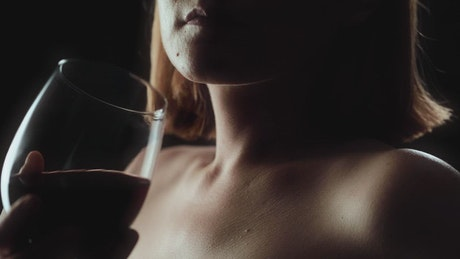 Woman drinking wine from a glass on a black background