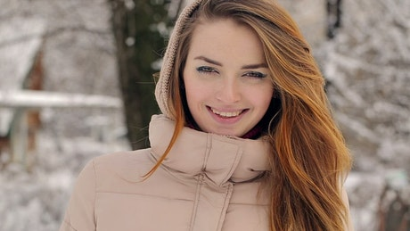Woman during winter watching and smiling at camera