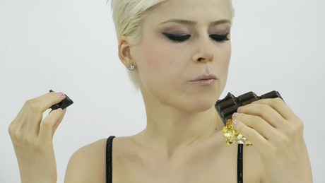 Woman eating a lot of chocolate