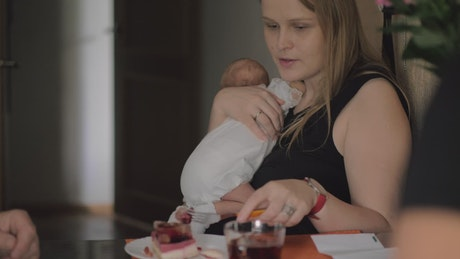 Woman eating breakfast while holding her baby