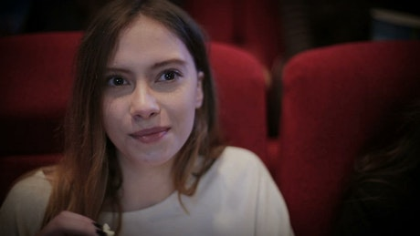 Woman eating popcorn at the cinema