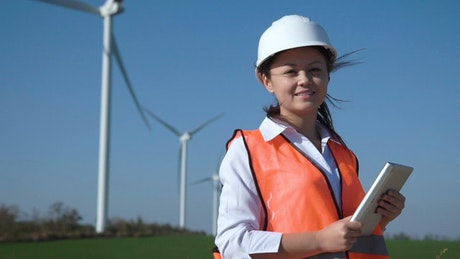 Woman engineer is smiling and holding a tablet