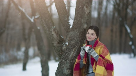 Woman enjoying a hot drink in the winter forest