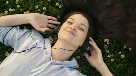 Woman enjoying listening to music in the garden