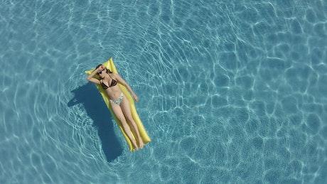 Woman enjoying summer sun at a pool