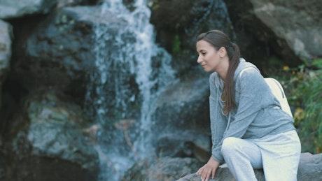 Woman enjoying the shore of a waterfall
