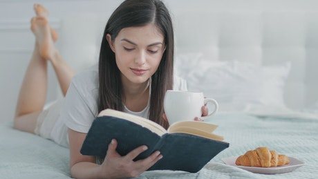 Woman enjoys book and breakfast in bed