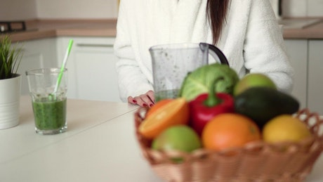 Woman enjoys healthy green smoothie in kitchen