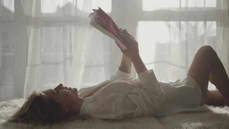Woman enjoys reading hobby by sunny window