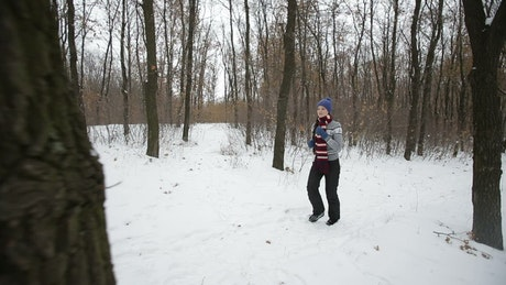 Woman exercising in a winter forest