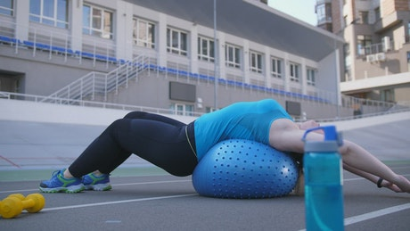 Woman exercising lying on a ball