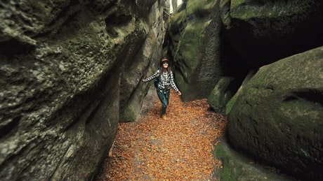 Woman exploring a cave in the forest