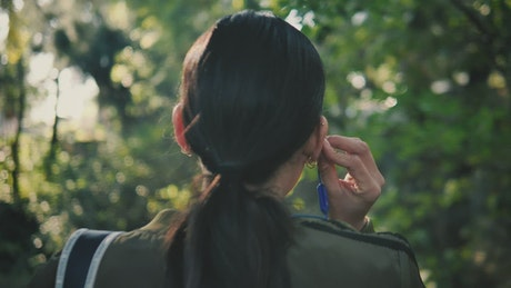 Woman form behind puts on headphones