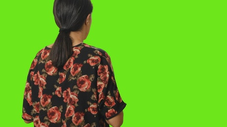 Woman from behind taking a photo on a green background