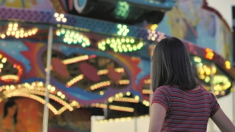 Woman from the back looking towards a mechanical game with lights