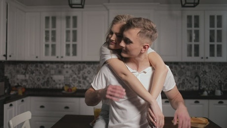 Woman gives man thank you hug in kitchen