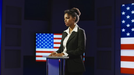 Woman giving a speech with flag in the background