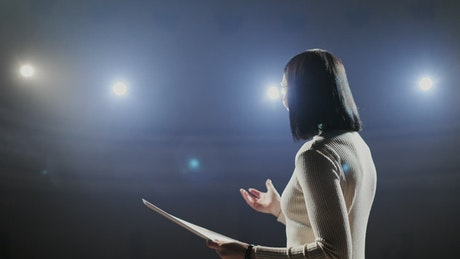Woman giving motivational talk on dark stage with bright lights