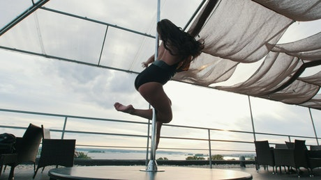 Woman giving twists while practicing pole dance