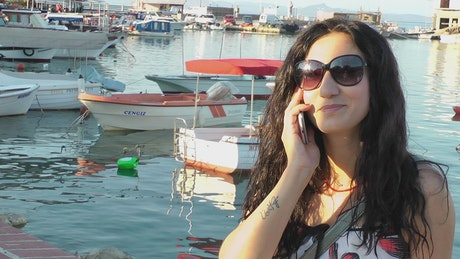 Woman having a call by the port