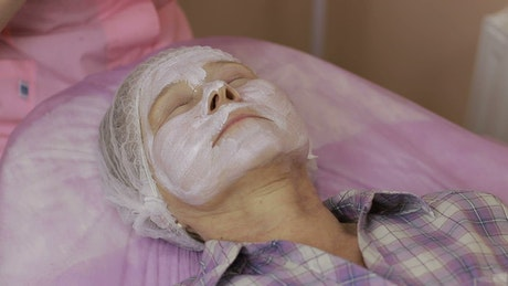 Woman having a face treatment applied