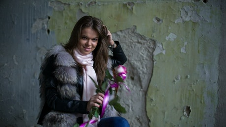 Woman holding a purple and white flower