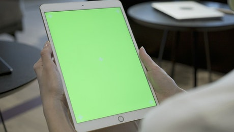 Woman holding a tablet with a chroma key screen