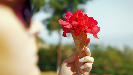 Woman holding a waffle cone with flowers