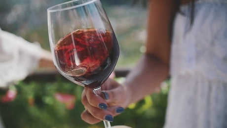 Woman holding a wine glass at a vineyard