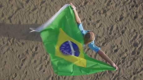 Woman holding the Brazilian flag in the wind