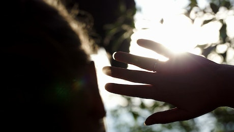 Woman holding up her hand to block the sun