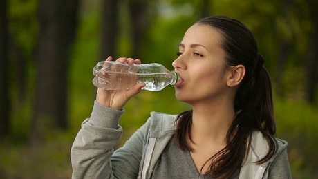 Woman hydrating after exercising