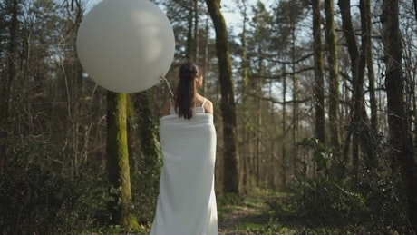 Woman in a forest with a balloon