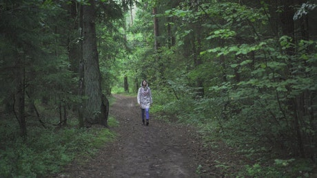 Woman in a hoodie walking in the forest