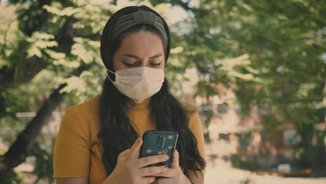 Woman in a mask sends messages on her smart phone