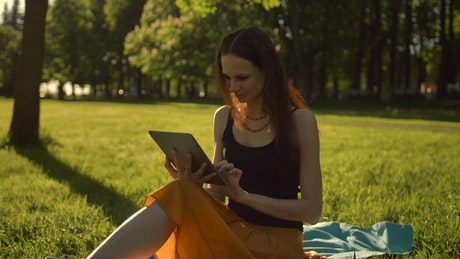 Woman in a park entertained on a tablet