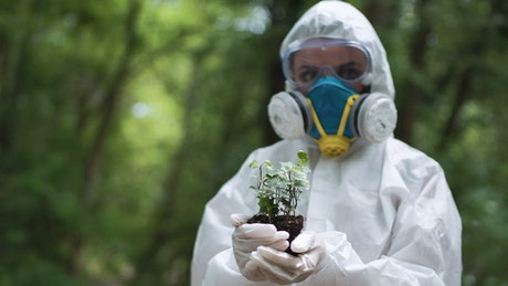 Woman in a protection suit holding a plant
