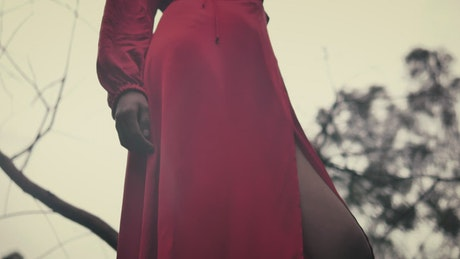 Woman in a red dress viewed from below with the sky in the background