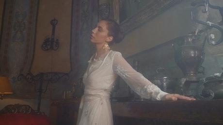 Woman in a white dress models beside wodden furniture