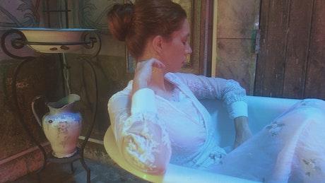 Woman in a white dress models in a bathtub