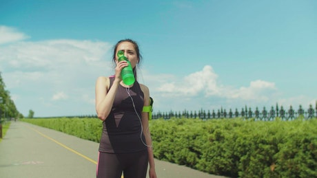 Woman in activewear drinking water after running