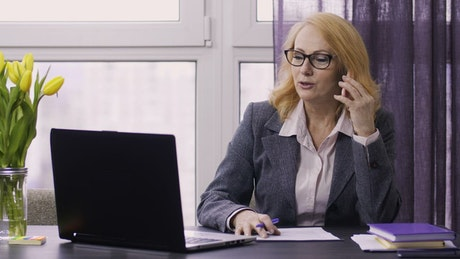 Woman in an office taking note during a phone call