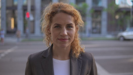 Woman in blazer on the street, smiling in the foreground