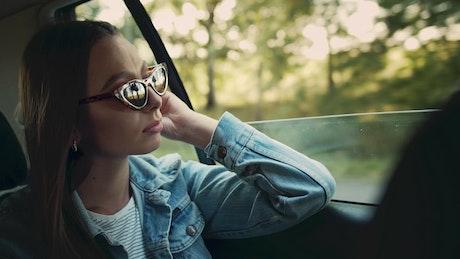 Woman in denim jacket gazes out car window