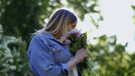 Woman in denim jacket smelling flowers on spring day