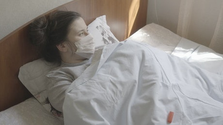 Woman in face mask checks thermometer while in bed