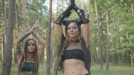 Woman in fantasy costumes belly dance in woods