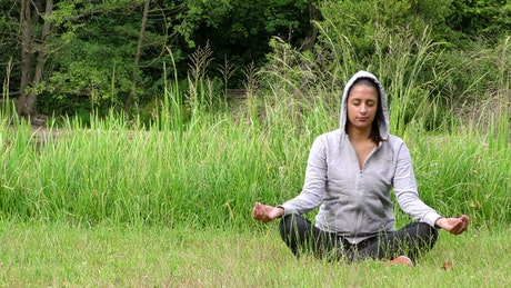 Woman in hoodie meditating on the grass