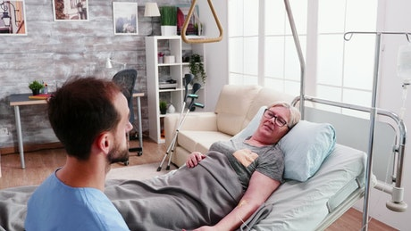 Woman in hospital bed comforted by nurse