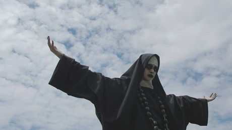 Woman in nun costume on a cloudy day